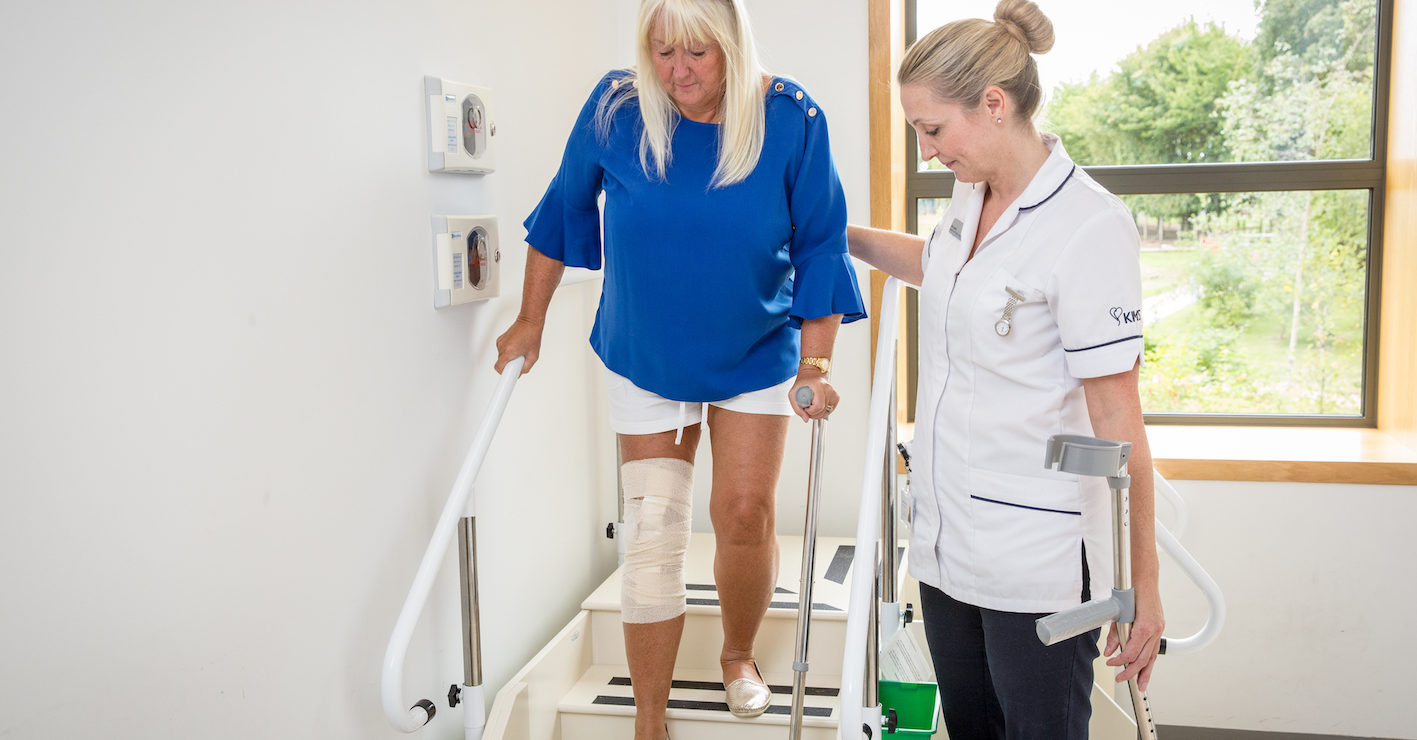 Inpatient physiotherapist taking knee replacement patient through exercises