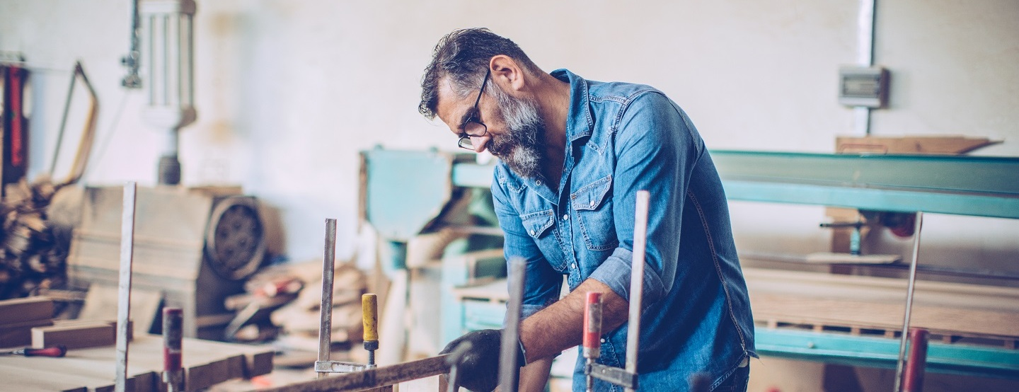 grey bearded man in denim shirt at work bench